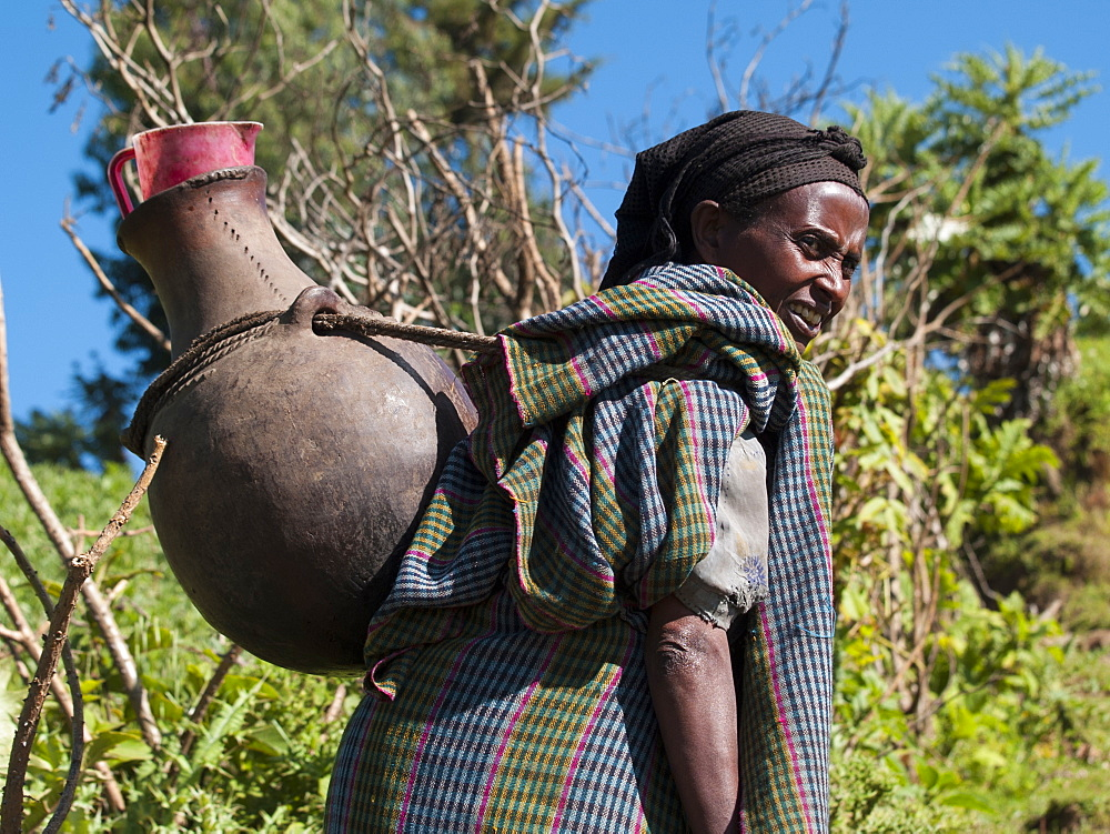 A woman carrying a large traditional pot of water on her back, Ethiopia, Africa