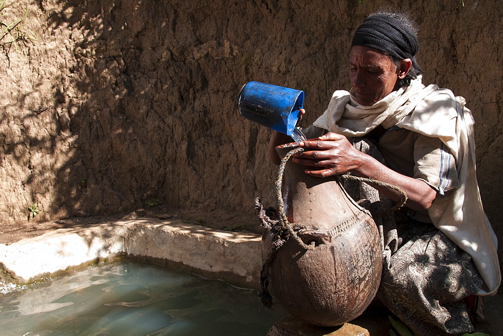 A woman fills a traditional water pot from a capped spring, Ethiopia, Africa