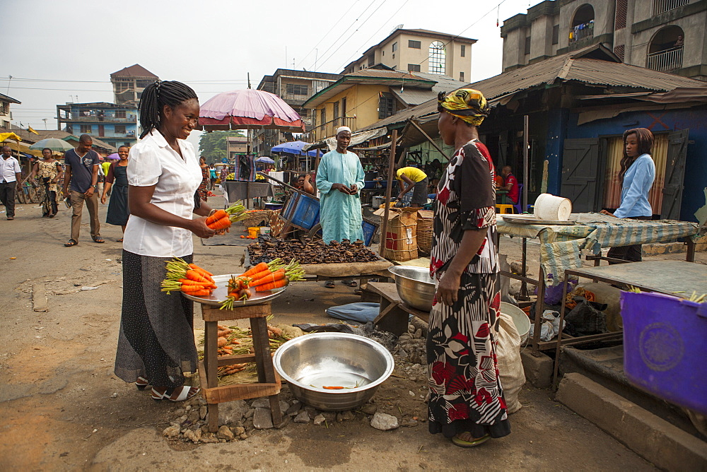 A woman buying carrots in the market in Nigeria, West Africa, Africa