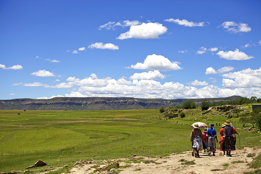 A group of woman walking through the rural countryside of Lesotho under a big blue sky.