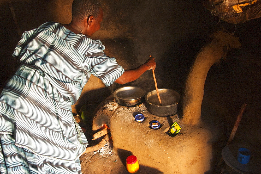 A woman cooking on a fuel efficient stove inside a traditional mud hut kitchen, Uganda, Africa