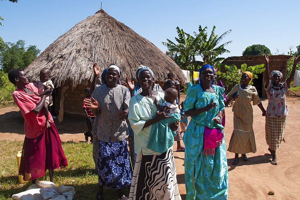 A group of women singing and dancing outside a traditional mud hut with a thatched roof.