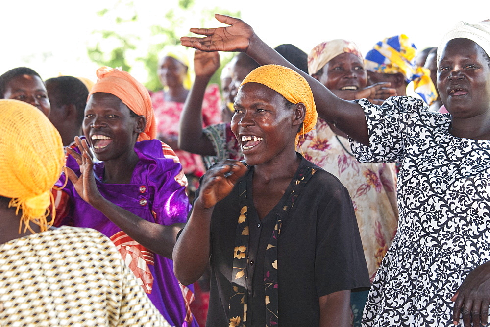 A group of women singing and dancing.