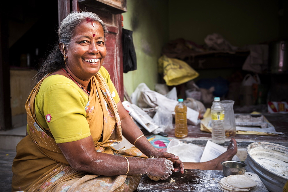 Portrait of an Indian woman making chapati in Fort Kochi (Cochin), Kerala, India, Asia