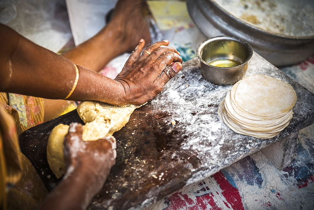 Portrait of an Indian woman making chapati in Fort Kochi (Cochin), Kerala, India, Asia