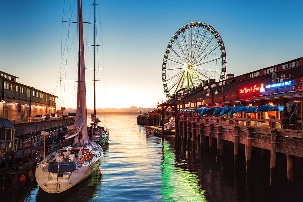 Sunset over mountains with Seattle Great Wheel on Pier 57 in the foreground. Seattle, Washington State, United States of America, North America