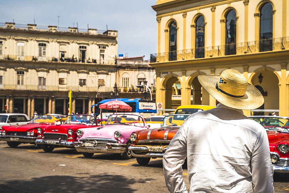 Cuban man overlooking colourful old American taxi cars parked in Havana, La Habana, Cuba, West Indies, Caribbean Central America