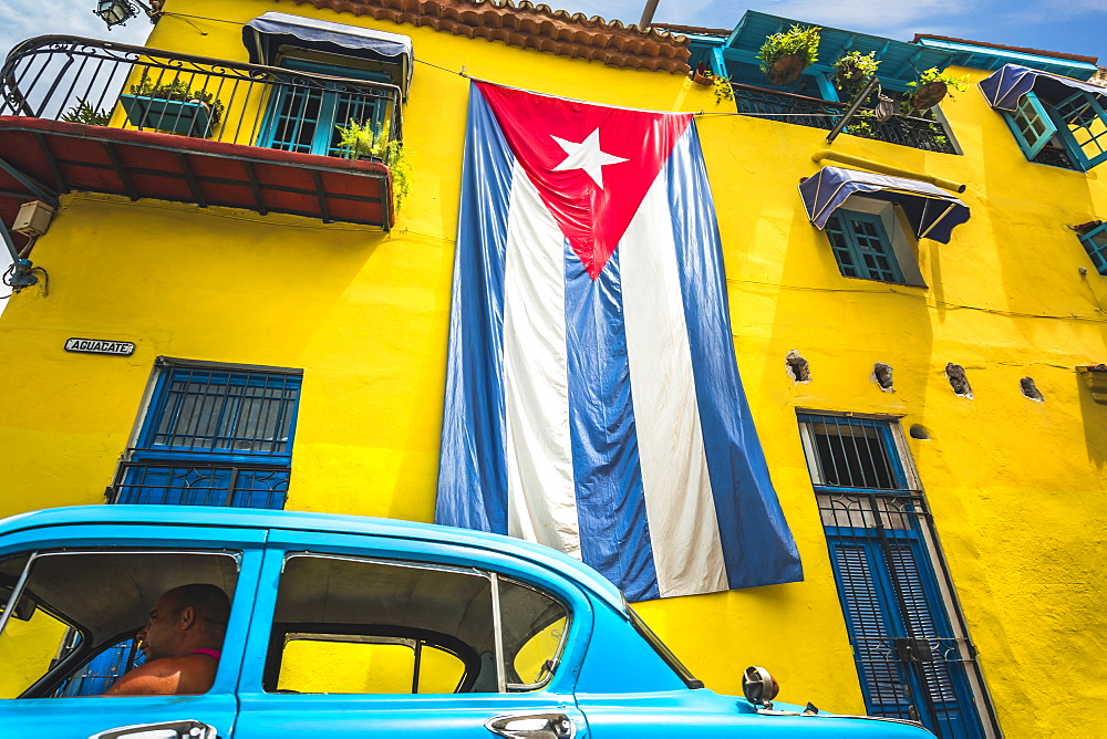 Old American classic car and huge Cuban flag on yellow building in Havana, La Habana (Havana), Cuba, West Indies, Caribbean, Central America