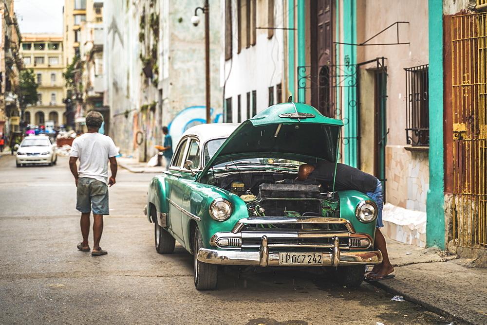 Local fixing his broken down American vintage car, La Habana, Havana, Cuba, West Indies, Caribbean, Central America