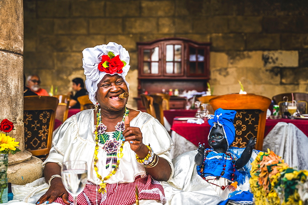Cuban woman posing for photos while smoking big Cuban cigar in La Habana, (Havana), Cuba, West Indies, Caribbean, Central America