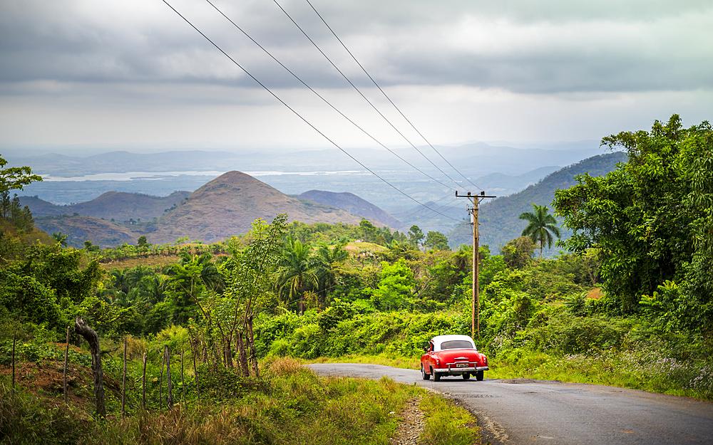 Old vintage American car on a road outside Trinidad, Sancti Spiritus Province, Cuba, West Indies, Caribbean, Central America