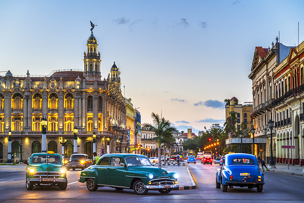 Vintage American cars turningand The Gran Teatro de La Habana at dusk, UNESCO, Havana, Cuba, West Indies, Caribbean