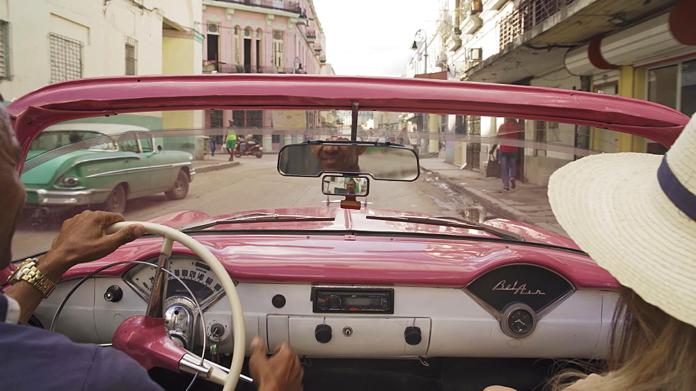 Local classic car driver showing Havana at sunset, Cuba, West Indies, Caribbean, Central America