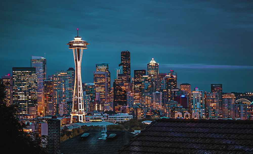 Seattle city skyline at night with urban office buildings and Space Needle viewed from garden near Kerry Park. Washington, USA