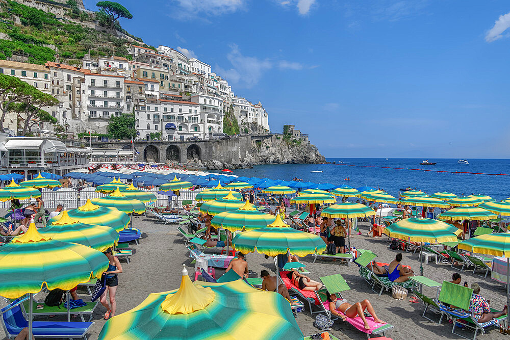 Amalfi Town, Italy daily beach view with bathers and colorful umbrellas before low rise buildings in Costiera Amalfitana. - 1278-231