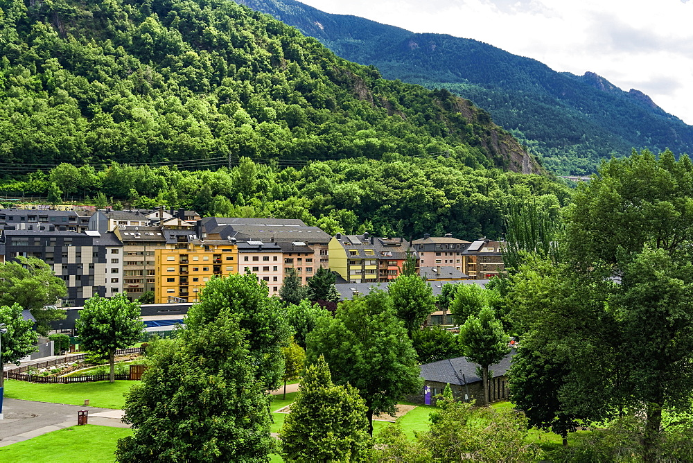 Day view of local buildings by a green hill in Andorra la Vella, capital of the Principality of Andorra, Europe