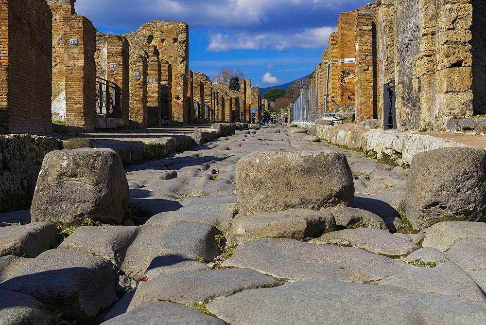 Pompeii, Italy street paved in a cobblestone fashion. Main ancient city street with stepping stones, raised blocks and houses.