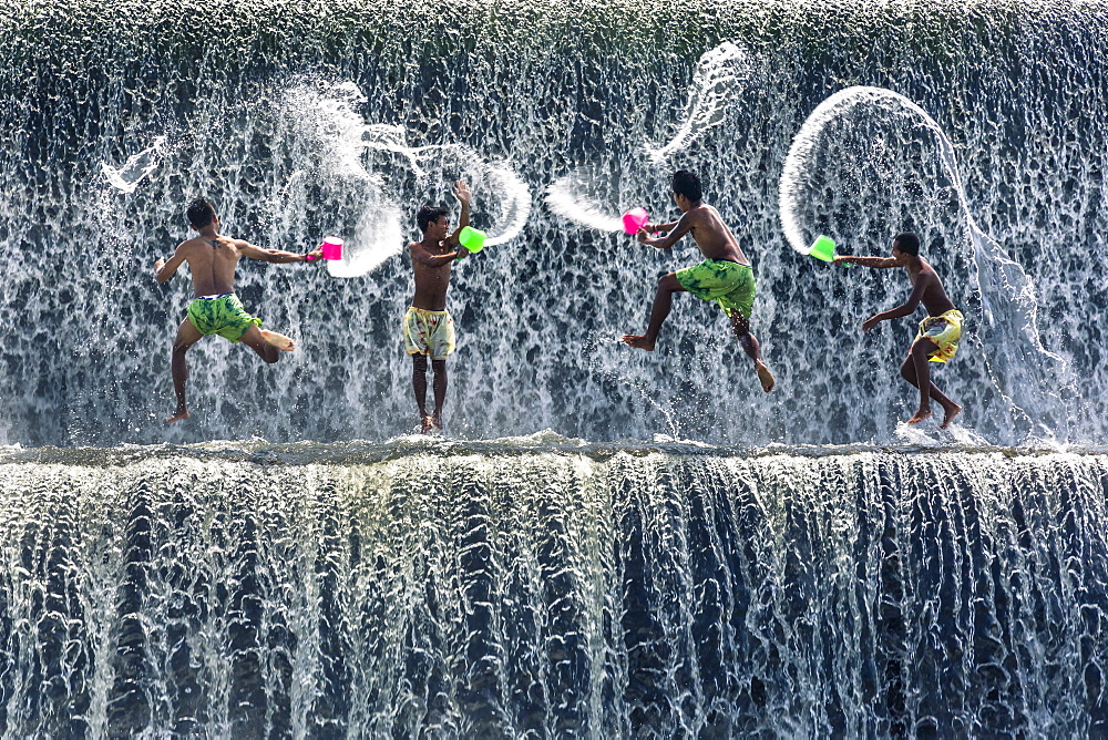 Boys water fight, Tukad Unda dam, Bali, Indonesia, South East Asia.