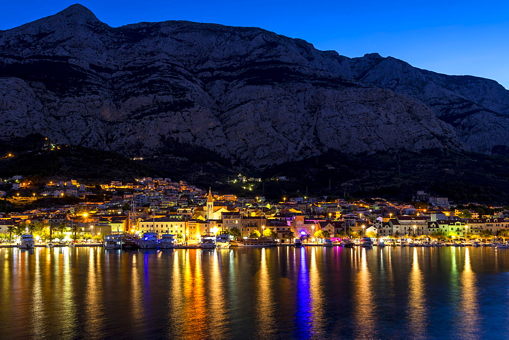 Cityscape of Makarska with Biokovo mountain range in the background at dawn