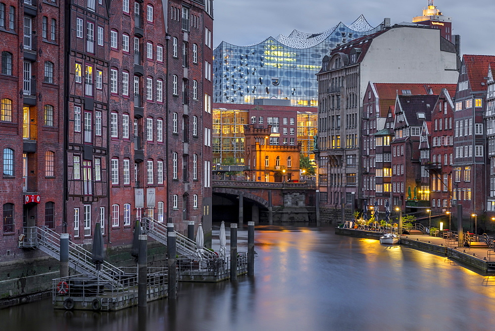 Historical buildings at Nikolaifleet with view to the Elbphilharmonie building in the background at dusk
