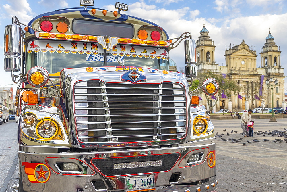 A typical chicken bus standing at the main square of Guatemala City with view to the Metropolitan Cathedral in the background, Guatemala City, Guatemala, Central America