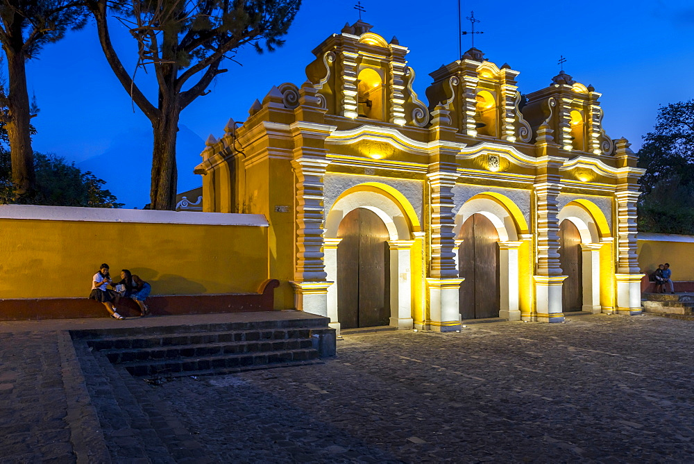 Illuminated entrance gate of the chapel El Calvario near Antigua at dusk, Guatemala, Central America