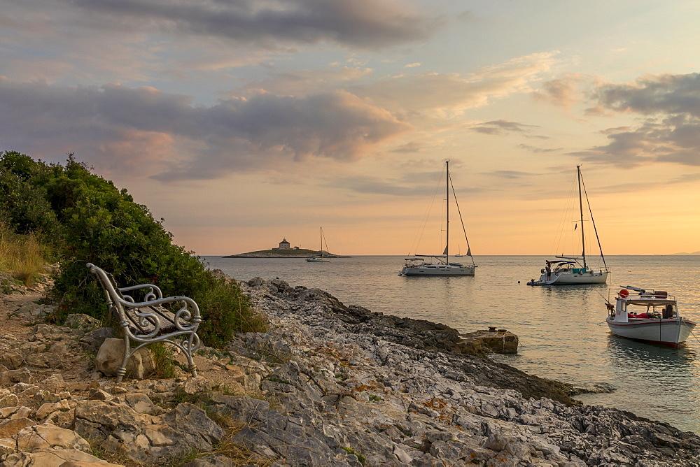 Boat anchoring at Pokonji Dol Beach near Hvar Town at sunset, Hvar, Croatia, Europe