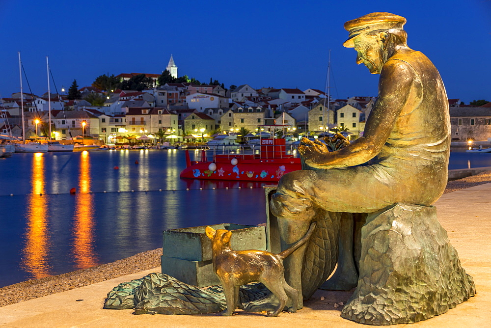 Fisherman statue with view to the old town of Primosten in the background, Croatia, Europe