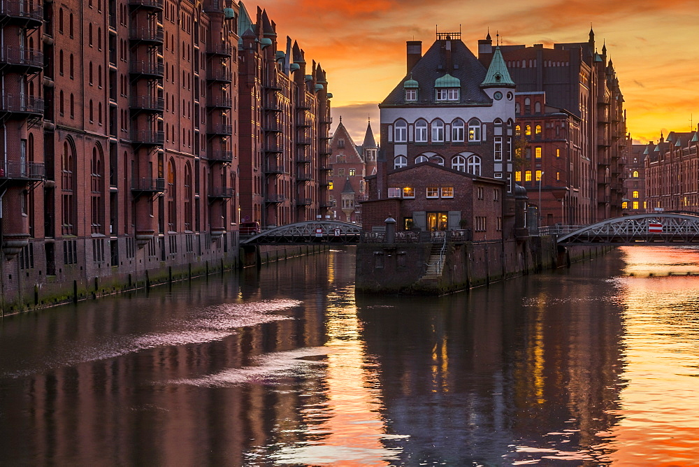 Wasserschloss building at the historical warehouse complex (called Speicherstadt) seen from Poggenmuehlenbruecke during sunset