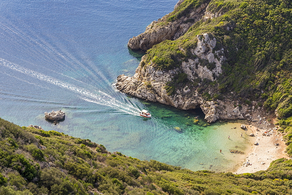 High-angle view down to one of the Porto Timoni beaches and a taxi boat approaching the bay, Afionas, Corfu, Greece, Europe