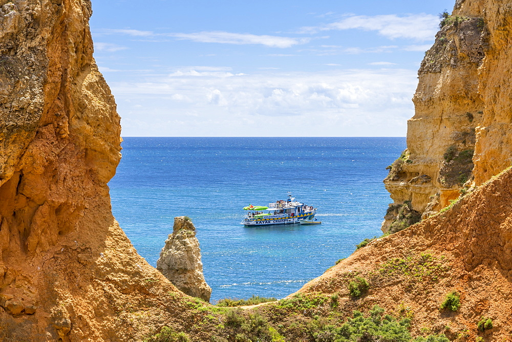 Excursion boat passing the rocky coastline near Lagos, Algarve, Portugal, Europe