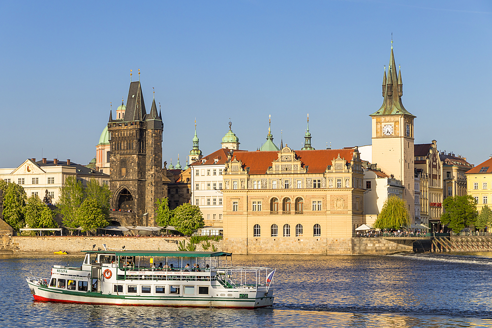 Tourist boat on Vltava River passing the Old Town Bridge Tower and the Old Town Water Tower, Prague, Bohemia, Czech Republic, Europe