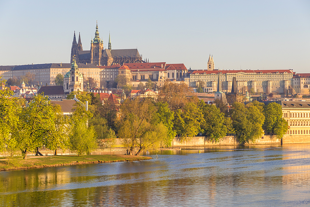 Prague Castle and St. Vitus Cathedral seen from the banks of Vltava River at first sunlight, Prague, Bohemia, Czech Republic