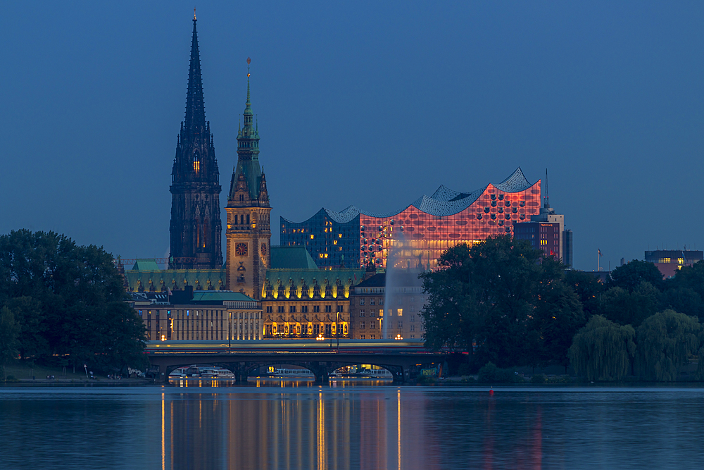 View from the Outer Alster Lake to the Elbphilharmonie, the town hall and St. Nikolai Memorial at dusk, Hamburg, Germany, Europe