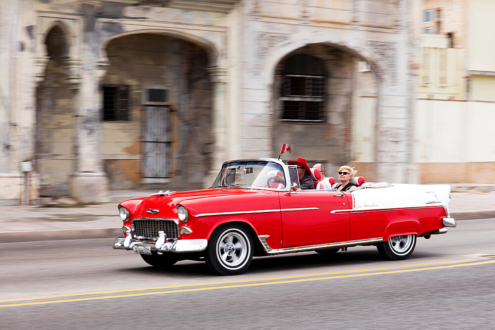 Red and white vintage American taxi driving along the Malecon, Havana, Cuba, West Indies, Caribbean - 1284-169