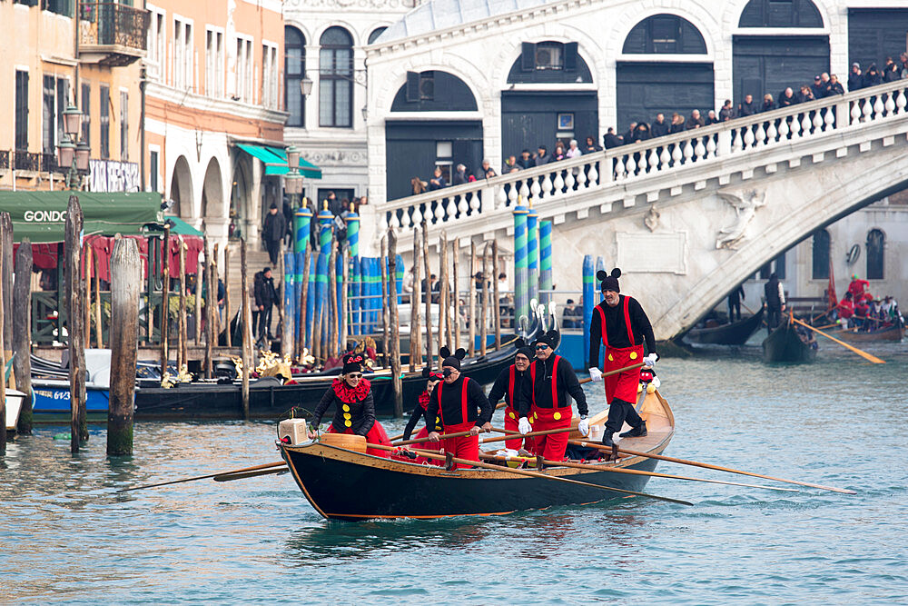People in Mickey Mouse Venice Carnival costumes, rowing gondola on Grand Canal by Rialto Bridge, Venice, UNESCO World Heritage Site, Veneto, Italy, Europe
