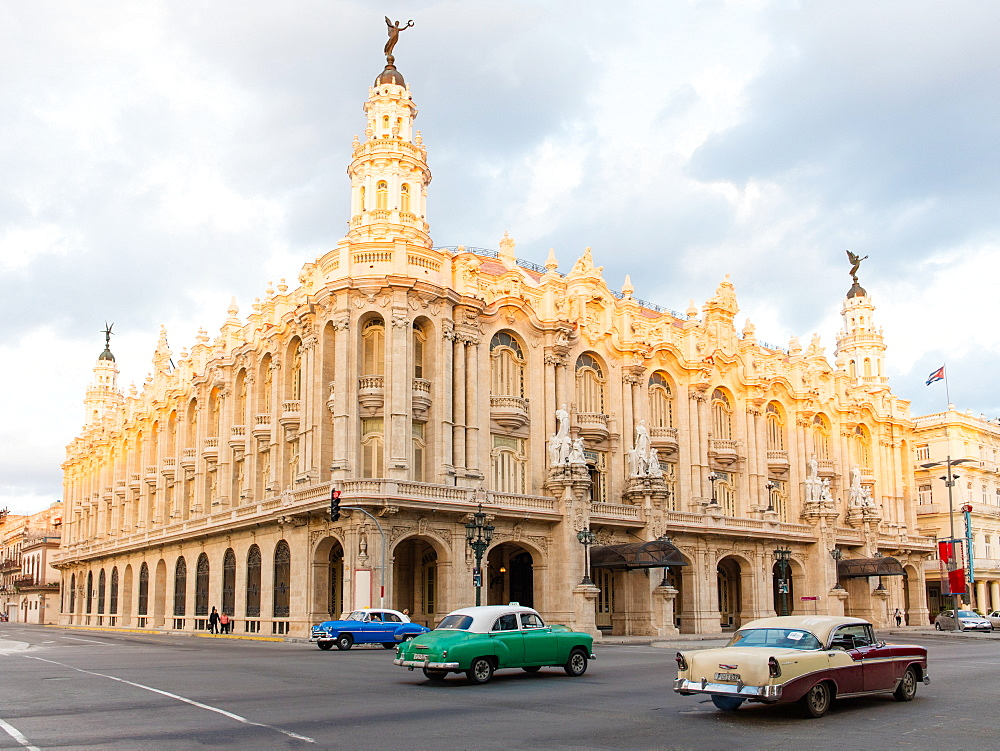 Old American cars drive past the Gran Teatro de La Habana in Havana, Cuba, West Indies, Caribbean, Central America