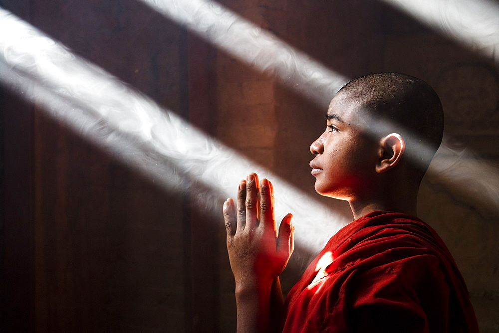 Young monk praying and covered with light beams in a temple in Bagan, Myanmar (Burma), Asia