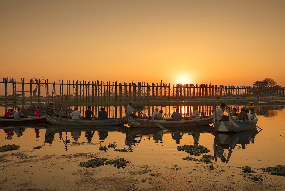 Sunset at U Bein bridge, oldest and longest teak bridge in the world, across Lake Taungthaman, Amarapura, Myanmar (Burma), Asia