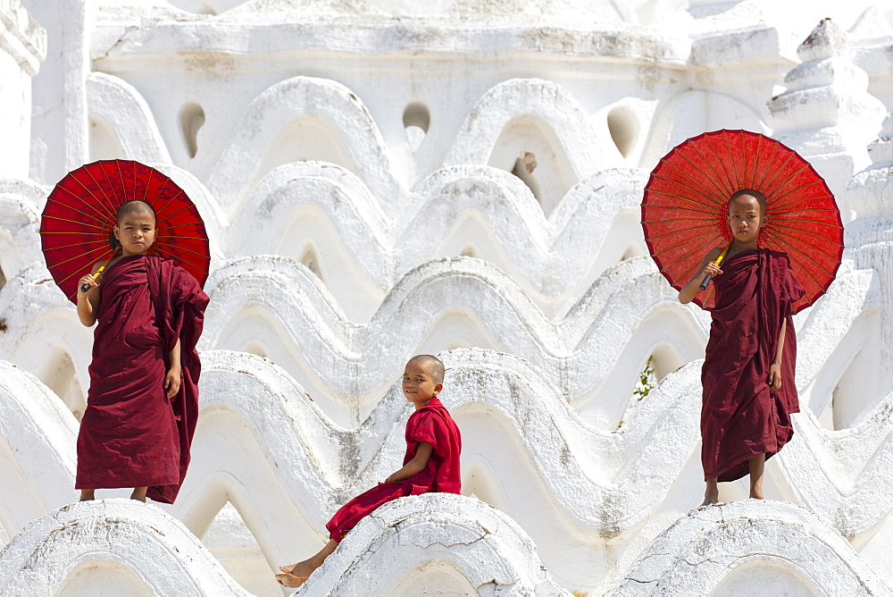 Three young monks dressed in red, with red parasols at the Myatheindan Pagoda (White Temple) in Mingun, Myanmar (Burma), Asia
