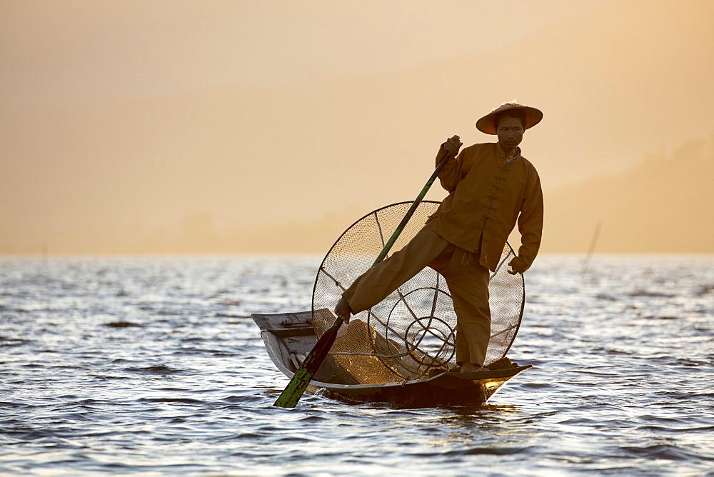 A fisherman rowing with one leg at sunset on Inle Lake, Myanmar (Burma), Asia