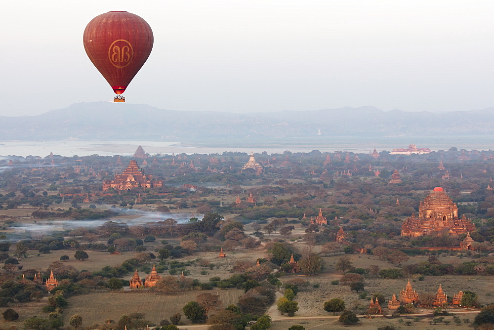 Hot air balloon flies over ancient Buddhist temples at dawn, Bagan (Pagan), Mandalay Region, Myanmar (Burma), Asia