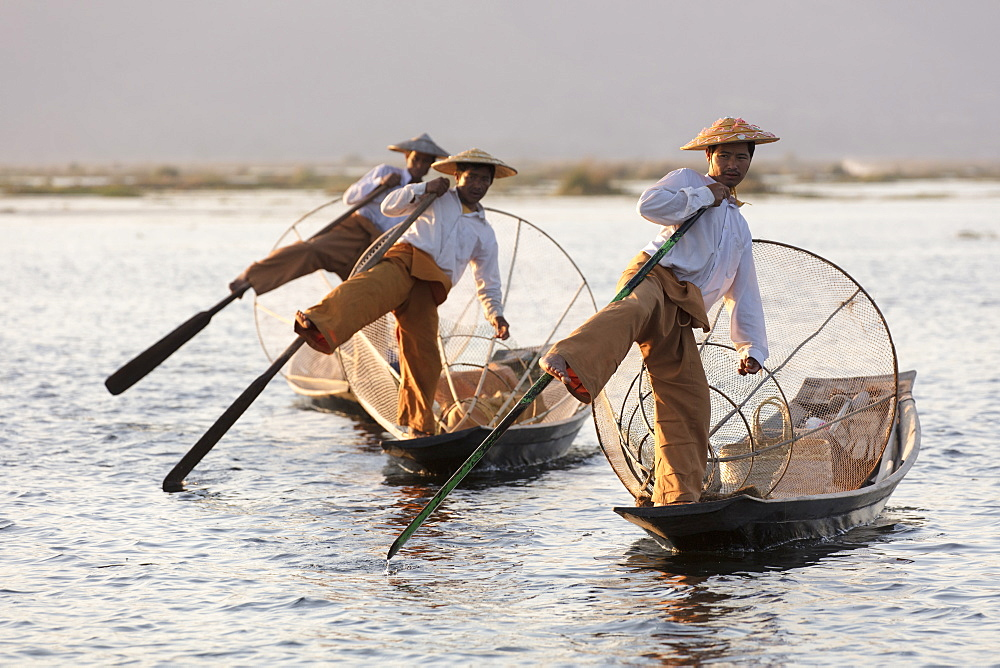 Three fishermen row with one leg at sunset on Inle Lake, Shan State, Myanmar (Burma), Asia