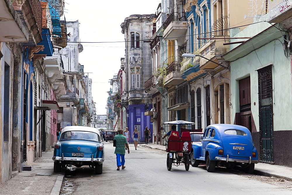 People walking past vintage American cars parked on street in Havana, Cuba, West Indies, Caribbean, Central America - 1284-94