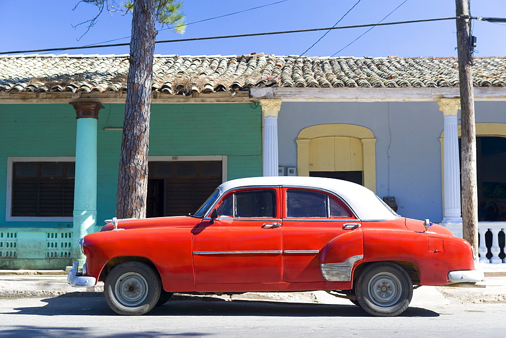 Red vintage American car parked on street next to colourful buildings in Vinales, Cuba, West Indies, Caribbean, Central America
