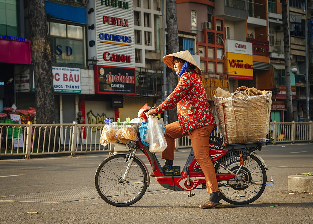 Vietnamese woman on bike crossing the road, Ho Chi Minh City, Vietnam, Indochina, Southeast Asia, Asia