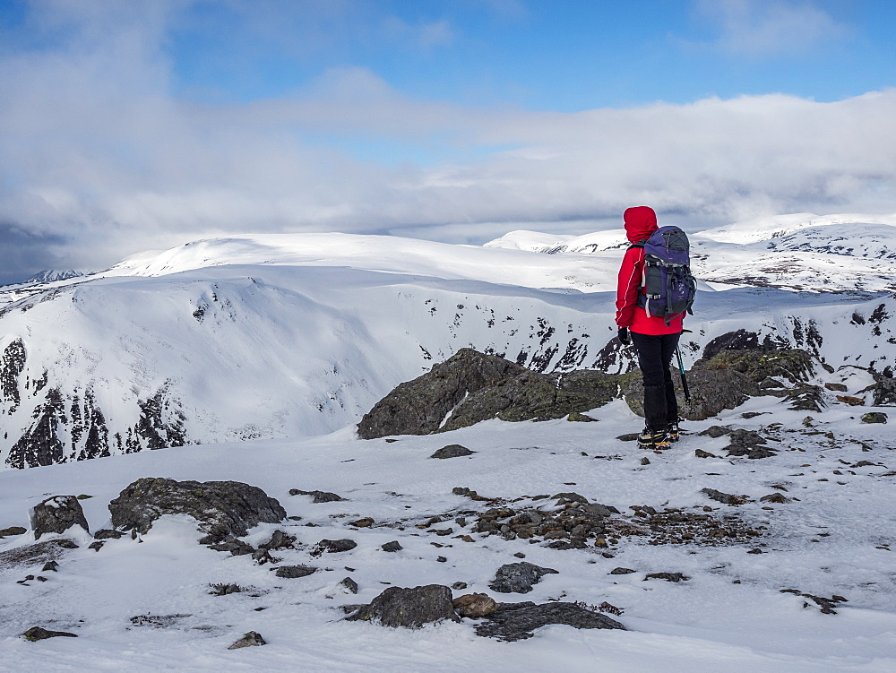 A winter walker on the summit of The Cairnwell in the Cairngorm National Park looking over to Carn a' Gheoidh, Cairngorm National Park, Scotland, United Kingdom, Europe