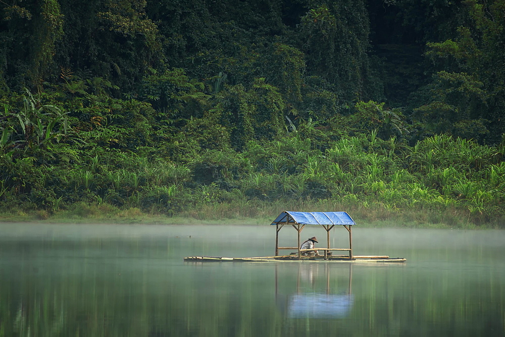 Boatman waiting in the middle of the lake at Situgunung Lake, West Java, Indonesia, Southeast Asia, Asia
