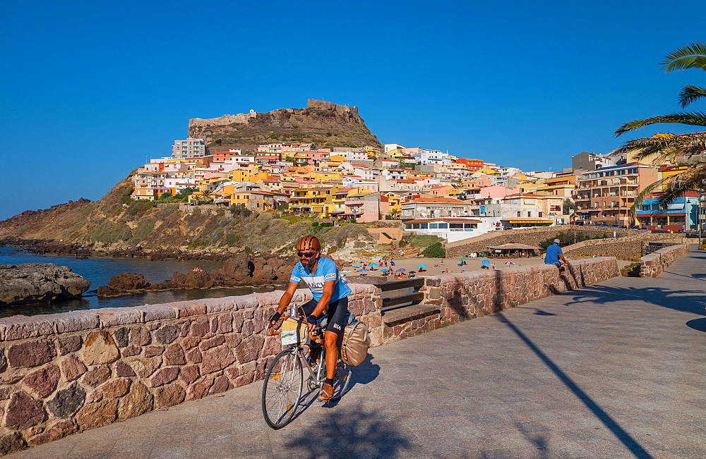 Cyclist on waterfront in Castelsardo, Sardinia, Italy, Europe