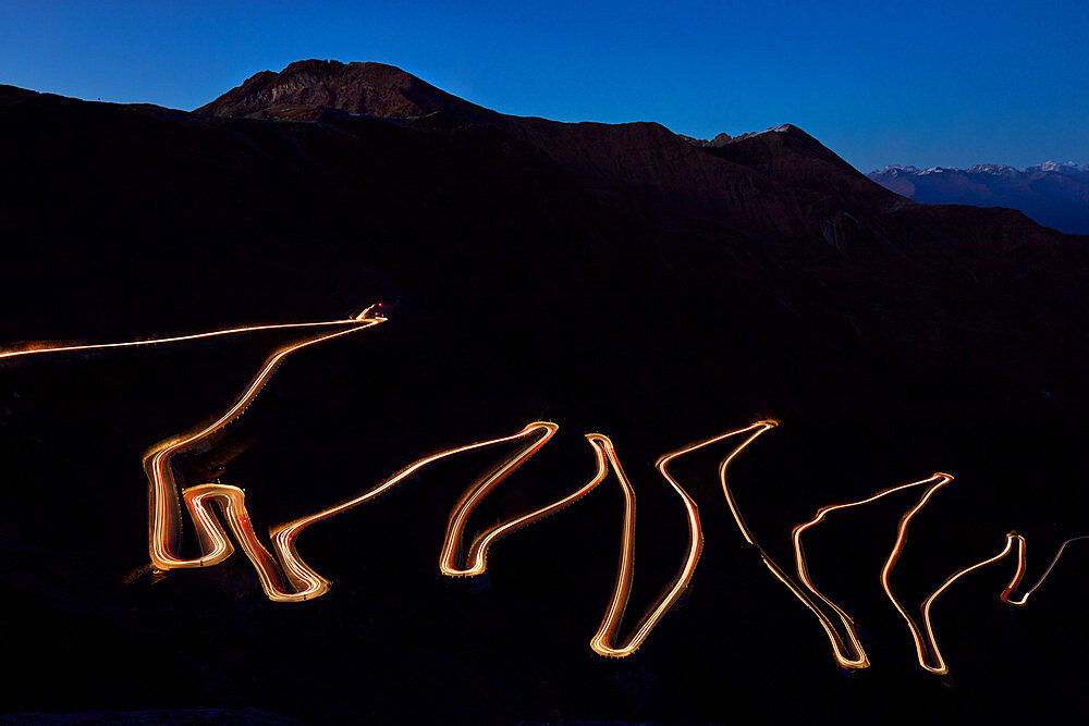 Pass road Stilfser Joch at night with light band of driving cars. Long time exposure - 1294-110